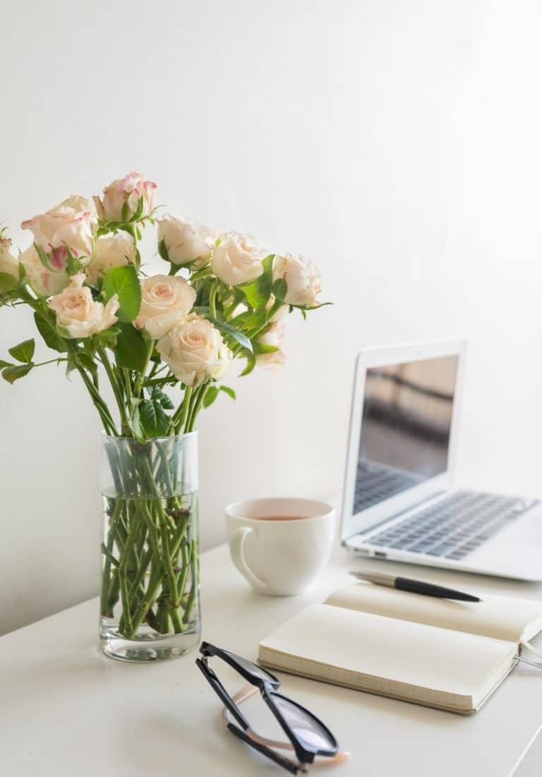 Una inspiradora imagen de cómo escribir contenidos SEO para posicionar un blog: junto a un bello ramo de flores, una taza de delicioso té, una libreta abierta y mi inseparable ordenador portátil.
