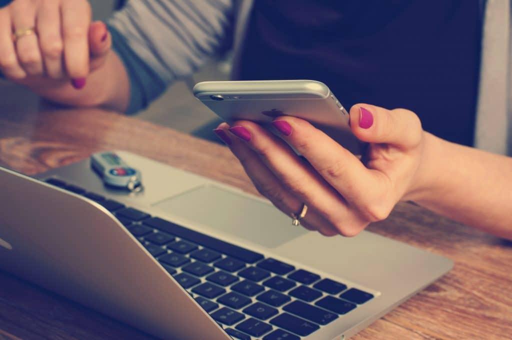 Mis manos sujetando un smartphone frente al ordenador. Diseño web responsive - Maria en la red